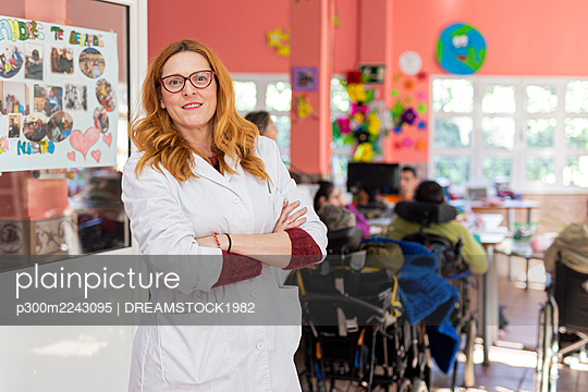 Redhead female caregiver with arms crossed in nursing home - p300m2243095 by DREAMSTOCK1982