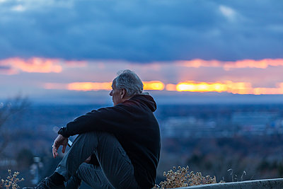 Seated man holding smart phone at sunset - p1427m2109961 by Steve Smith
