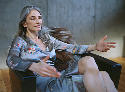 Portrait of mature woman sitting in armchair gesturing - p300m1549745 by Sandra Seckinger