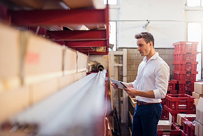 Young businessman in factory storeroom using tablet - p300m1562983 by Daniel Ingold