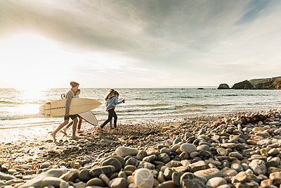 Happy friends with surfboards walking on stony beach - p300m2070820 by Uwe Umstätter