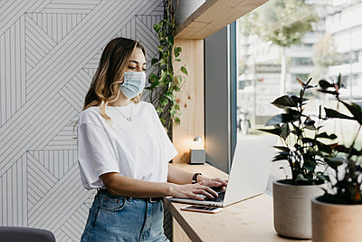 Woman wearing protective face mask using laptop while standing in cafe during covid-19 - p300m2226023 by letizia haessig photography