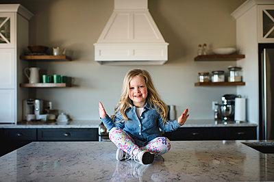 Portrait of girl sitting cross legged on kitchen counter - p429m1418415 by Erin Lester