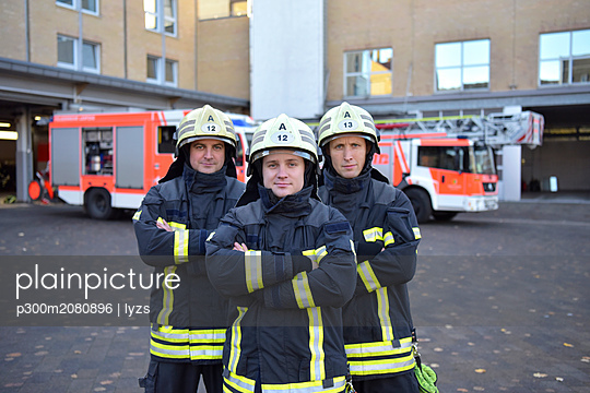 Portrait of three confident firefighters standing on yard in front of fire engine - p300m2080896 by lyzs