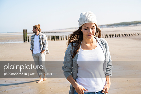 Thoughtful woman with hands in pockets at beach during sunny day - p300m2226518 by Uwe Umstätter