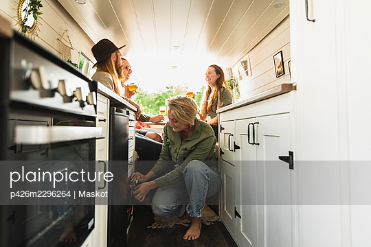 Male and female friends spending leisure time in motor home - p426m2296264 by Maskot