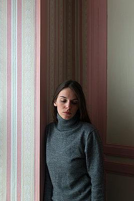 Melancholische Frau in grauem Pullover lehnt an einer Wand - p1096m1561799 von Rajkumar Singh