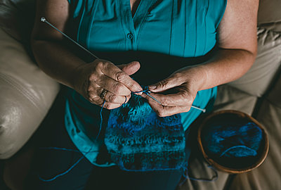 High angle midsection of woman crocheting while sitting on sofa at home - p1166m1521183 by Cavan Images