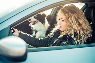 Woman driving car, dog sitting on passenger seat - p300m1115048f by OneInchPunch