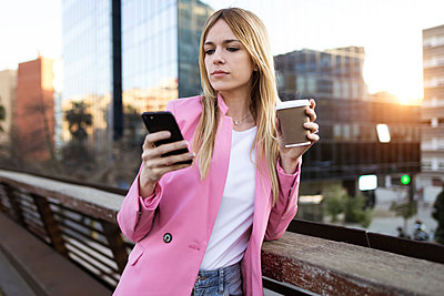 Young businesswoman using smartphone and holding coffee to go - p300m2114579 by Josep Suria