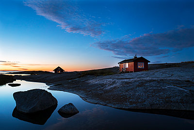 Wooden house on rocky coast - p312m1192734 by Peter Lyden