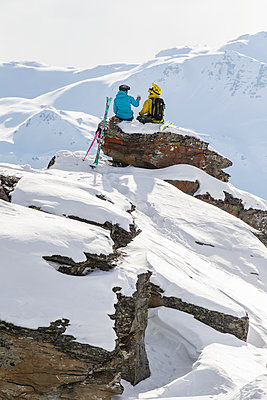 Two skiers resting and drinking water after a good ski run - p343m1217833 by Thomas Bekker
