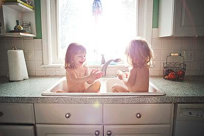 Twin girls bathing in kitchen sink - p555m1408925 by Shestock