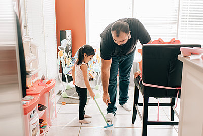Girl sweeping kitchen floor, father watching - p924m2090621 by Sara Monika