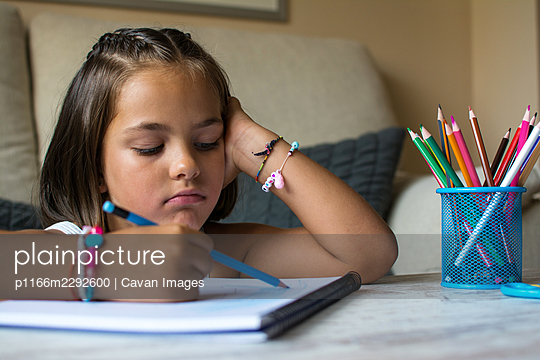Little Girl In The Living Room Doing Homework. Education At Home - p1166m2292600 by Cavan Images