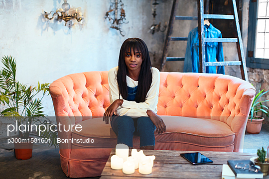 Portrait of young woman sitting on the couch in her loft - p300m1581601 von Bonninstudio