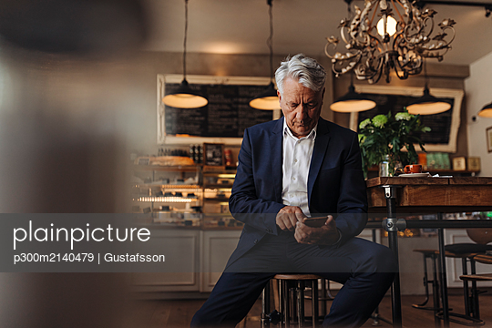 Senior businessman using cell phone in a cafe - p300m2140479 by Gustafsson