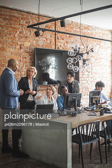 Business professionals discussing at startup company - p426m2296178 by Maskot