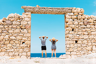 Greece, Milos, Firopotamos Beach, Couple standing in door in stone wall, looking at distance - p300m1205445 by Gemma Ferrando