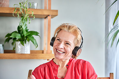 Thoughtful woman with headphones smiling at home - p300m2265249 by Jo Kirchherr