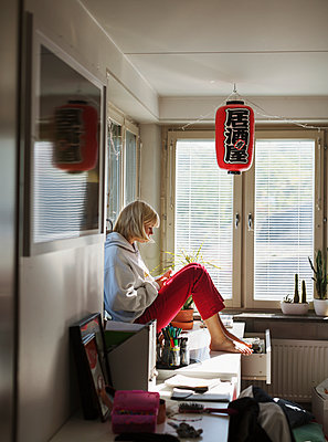 Teenage girl sitting on desk - p312m2080558 by Pernille Tofte