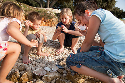 Children listening to shells at beach - p42910671f by Henglein and Steets