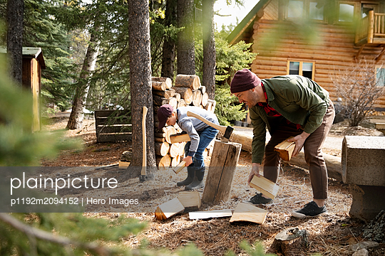 Father and son cutting firewood outside cabin - p1192m2094152 by Hero Images