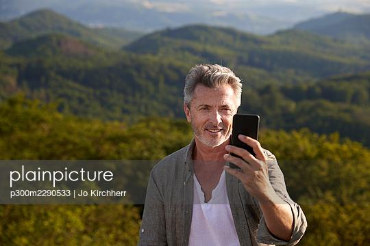 Smiling male hiker while talking selfie through smart phone - p300m2290533 by Jo Kirchherr