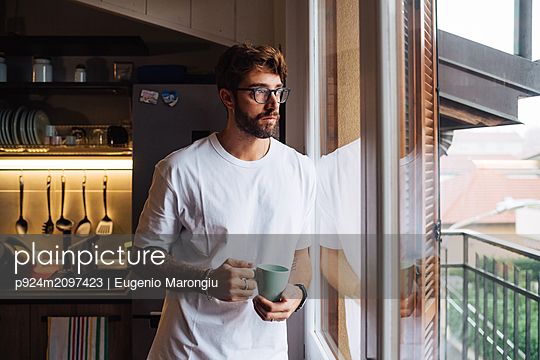 Mid adult man with coffee cup gazing out through apartment window - p924m2097423 by Eugenio Marongiu