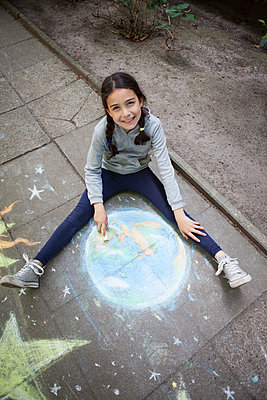 Mädchen malt Erde mit Kreide - p045m1588902 von Jasmin Sander
