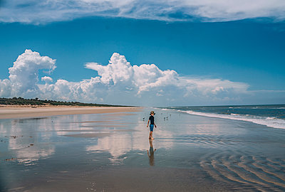 Boy standing at New Smyrna Beach against cloudy sky - p1166m1507807 by Cavan Images