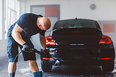 Worker pouring water with hose on car while standing in workshop - p1166m2060368 by Cavan Images