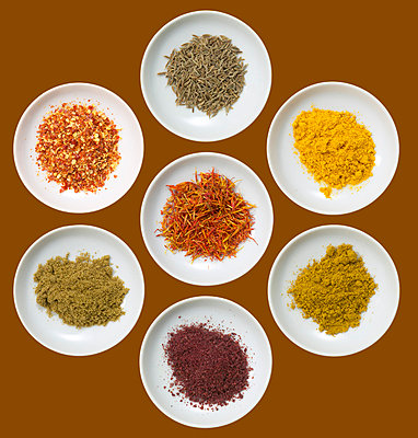 Variety of spices on plates, elevated view - p3007156f by Tom Hoenig
