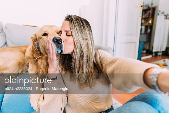 Italy, Young woman kissing dog at home - p924m2283024 by Eugenio Marongiu