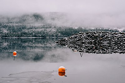 snow covered rocks, lake and forest with buoys in the water - p1166m2190894 by Cavan Images