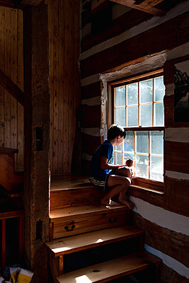Boy sitting on stairs of log cabin cottage looking out through window - p1166m2207991 by Cavan Images