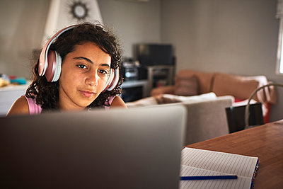 Close-up of a girl with headphones working with her laptop - p1166m2212890 by Cavan Images