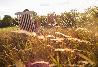 Back view of woman sitting on a deck chair on a meadow - p300m1068854f by Uwe Umstätter