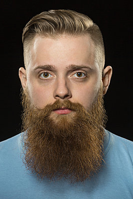 Close-up portrait of bearded man against black background - p301m1196823 by Vladimir Godnik