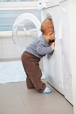 Little boy looking into washing machine - p5730296 by Birgid Allig