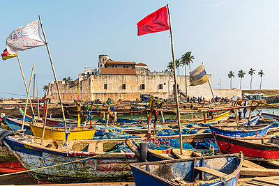Africa, Ghana, Elmina harbour. Traditional wooden fishing boats in the harbour in front of the famous castle. - p651m2085076 by Catherina Unger