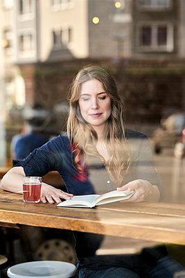 Frau im Cafe liest ein Buch - p890m1440026 von Mielek