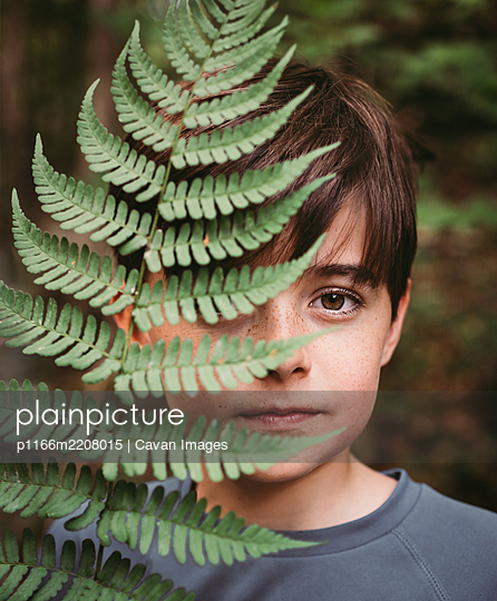 Portrait of young boy covering half of his face with a fern leaf. - p1166m2208015 by Cavan Images