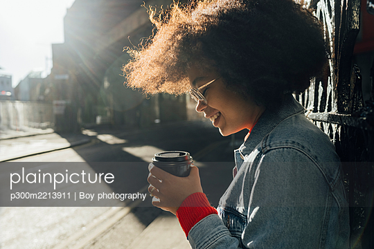 Close-up of smiling afro woman holding disposable cup on street during sunny day - p300m2213911 by Boy photography
