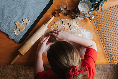 Young girl cutting out gingerbread dough on a wooden table - p1166m2212767 by Cavan Images
