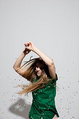 Junge Frau tanzt im Konfettiregen - p1212m1092888 von harry + lidy