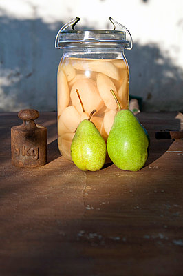 Preserving jar of sliced pears, two fresh pears and old weight - p300m1017682 by Gianna Schade