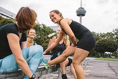 Four women relaxing after workout - p300m1081417f by Matthias Drobeck