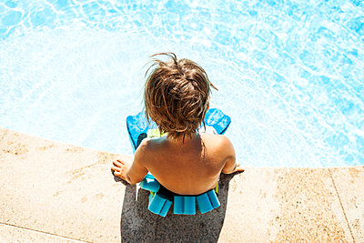 Back view of little boy with floating belt sitting at pool edge - p300m1205341 by Valentina Barreto
