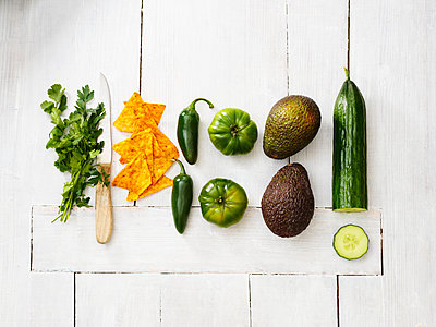 Avocados, green tomatoes, Jalapeno peppers, cucumber, parsley, kitchen knife and tortilla chips on white wood - p300m1568171 von Kai Schwabe